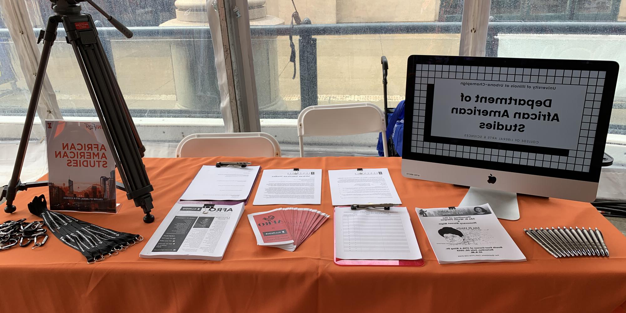 AFRO table setup at Illini Fest with brochures, sign up sheets, and merchandise such as pens, lanyards, and carabiner keychains.