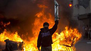 protester holding up skateboard in front of fires from the protests